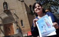 Artist Carlota EspinoZa holds a photo of her work last week in front of Our Lady of Guadalupe Church in Denver. Church parishioners have started a grassroots effort to protest a wall that has replaced EspinoZa's long standing mural in the building. (KRISTIN MORIN / YOURHUB)